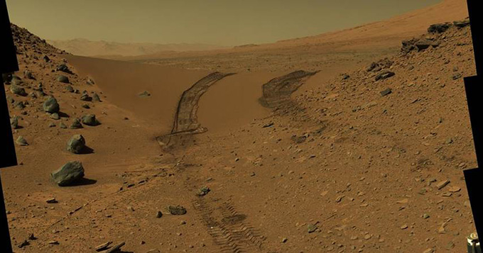 Vehicle tracks on yellow soil on surface of Mars