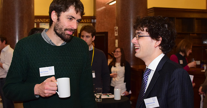 Two people networking at an event while drinking tea and coffee
