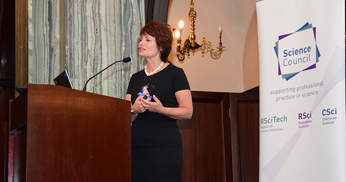 Professor Dame Anne Glover stands at a podium delivering a lecture