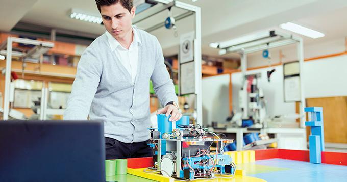 Male scientist building a robot