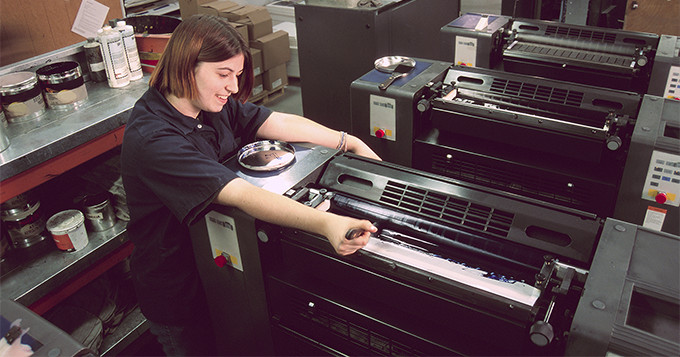 Female apprentice technician working a large print machine