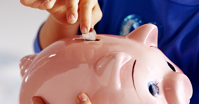 Person inserting a coin into a piggy bank
