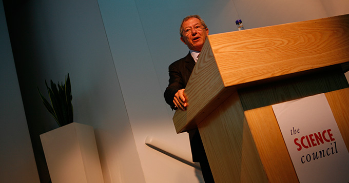 Professor Sir David King standing at a podium delivering a lecture