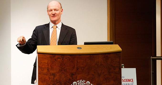 David Willetts MP standing at a podium delivering a lecture