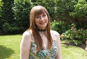 Sharon, Chartered Scientist, stands with a smile in a sunny garden