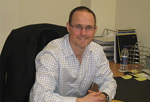 Tim, Chartered Scientist, sits with a smile at an office desk with his hands rested on the desk