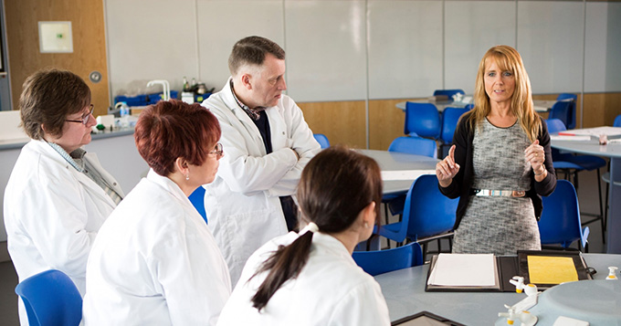 A woman who is not wearing a lab coat delivers a talk to a small group of people wearing lab coats
