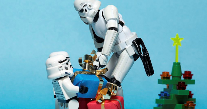 Three Storm Trooper Lego figures are carrying boxes of presents with a Lego Christmas tree in the background