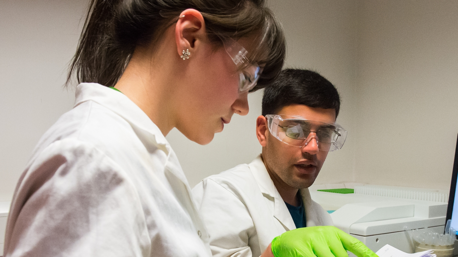 Science students in lab coats and safety glasses