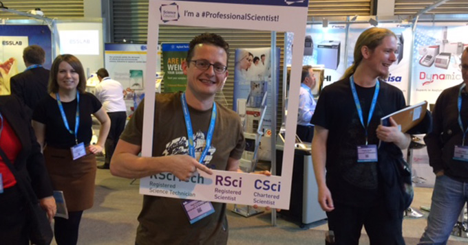 A registrant stands in a busy exhibition hall holding a professional scientist instaframe while pointing at some text on it which says 'RSci'