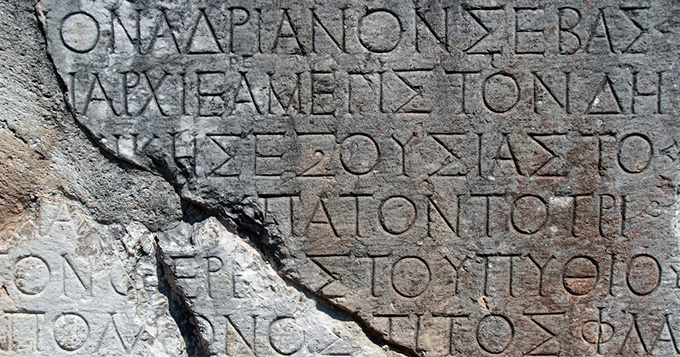 a grey stone tablet with Greek letters engraved