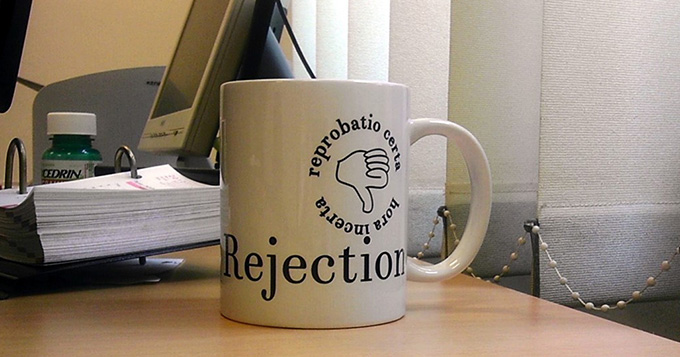 a mug on a desk - the mug has 'Rejection' written on it and a thumbs down