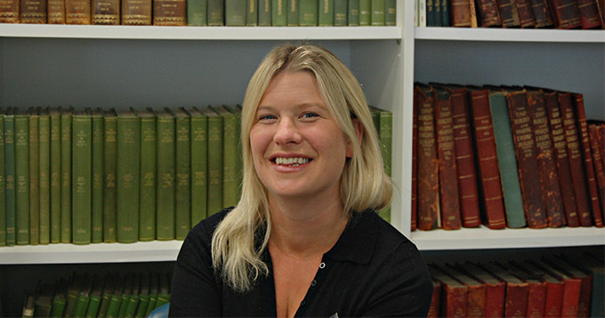 Dr Bev Mackenzie (Science Council trustee) sits with a smile in front of shelves of books