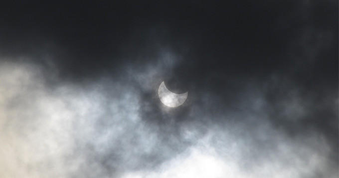 Solar eclipse covered in partial cloud with a crescent moon in sight.