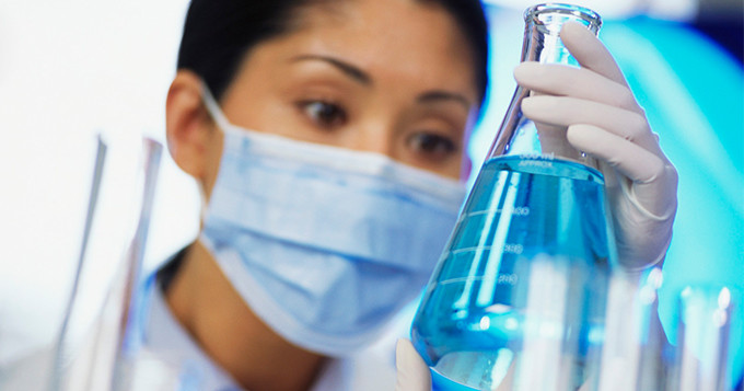 Female scientist looks at a flask containing bright blue liquid