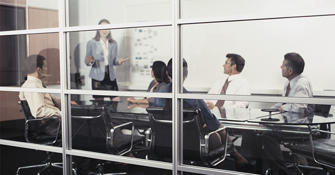 Boardroom meeting with photo taken looking through a glass wall, with male and female colleagues sitting inside