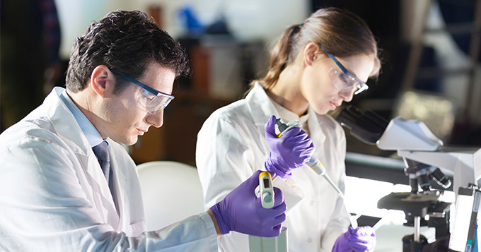 Male and female technician working in a lab.