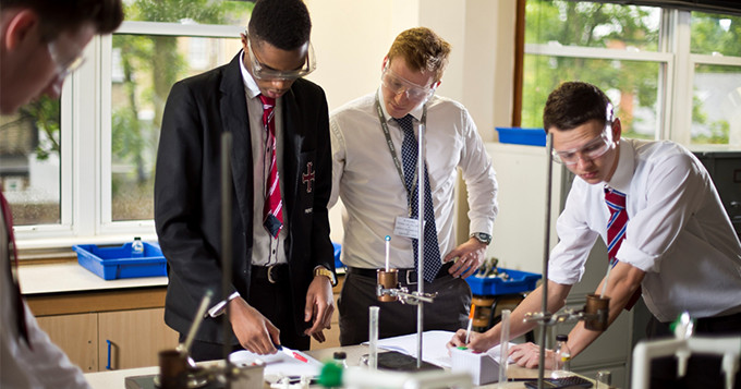 School and college students doing a science practical while being supervised by a teacher