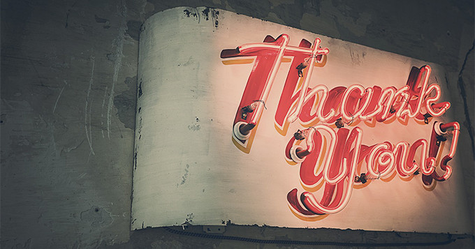 Thank you sign in neon lights against a dark wall