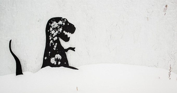 Graffiti of a dinosaur on a white wall