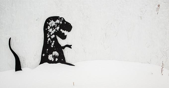 Graffiti of a dinosaur on a white wall