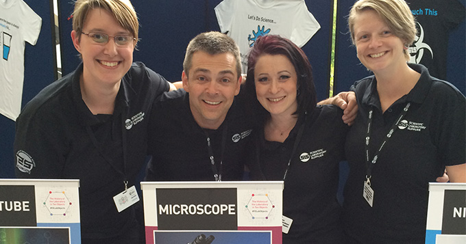 Four people wearing black SLS polo shirts standing behind a sign saying Microscope