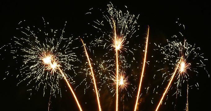 five exploding white fireworks against a dark sky