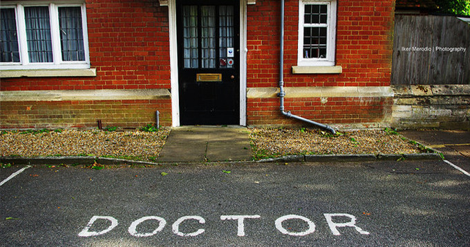 Front door of a doctor's surgery with reserved parking bay in front which has the word 'DOCTOR' written on the ground