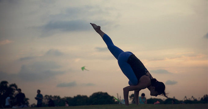Woman doing yoga in the park at sunset
