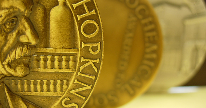Photo of half a gold coin with the word 'Hopkins'