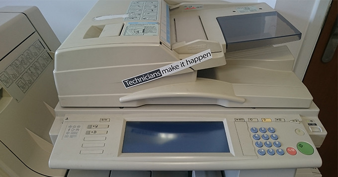 Office printer with 'Technicians Make it Happen' sticker