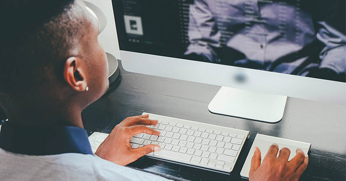 Computer scientist sitting at a desk working on his computer