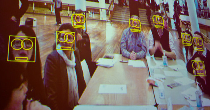 Image of a group of people looking into a camera showing their facial recognition