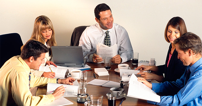 Men and women dressed in business attire having a meeting in a boardroom