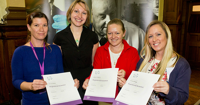 Four women standing together, 3 holding certificates that say Registered Scientist