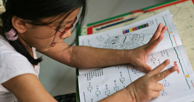 Girl counting numbers with her fingers while studying a maths workbook
