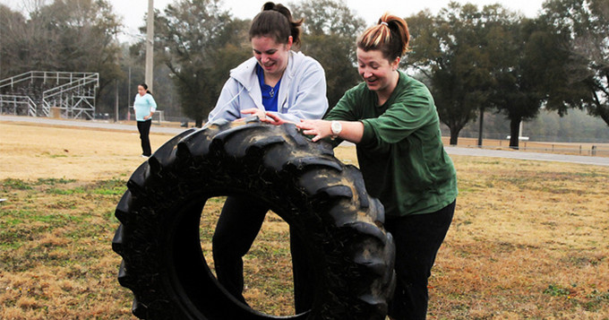 Two women rolling a large tyre as part of fitness bootcamp