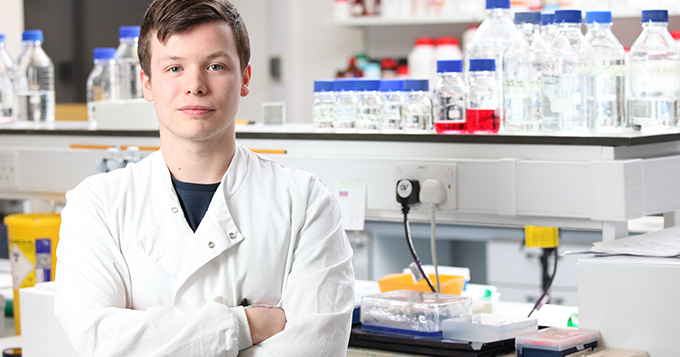 Young white man with brown hair wearing a white coat stands with arms folded and proud smile on his face in front of a laboratory bench