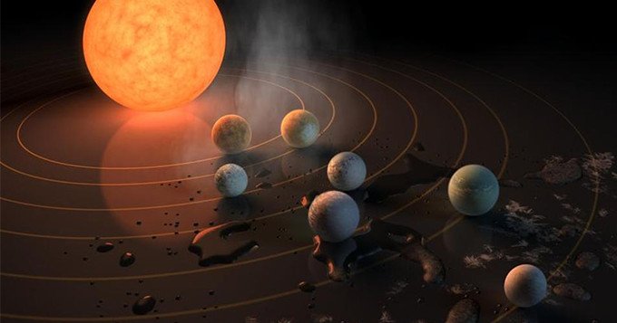 Artist concept drawing of TRAPPIST-1, a star with seven Earth-size planets orbiting it.