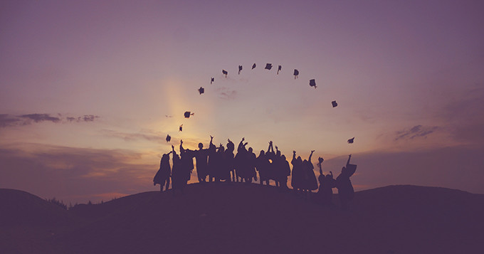 Graduates tossing their hats in the air while standing on a hill at sunset